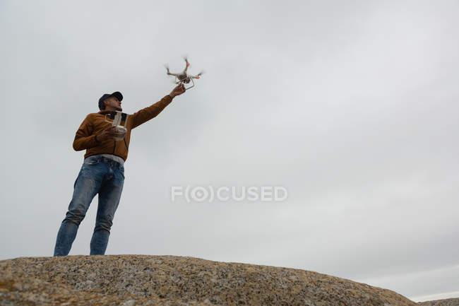 Uomo che aziona un drone volante su una roccia — Foto stock