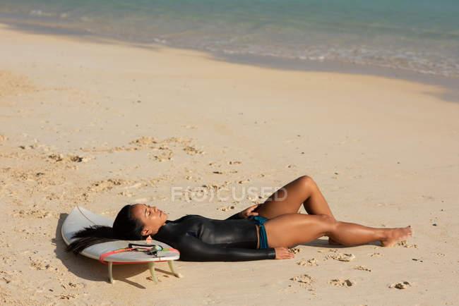 Женщина спит на доске для серфинга на пляже в солнечный день — стоковое фото