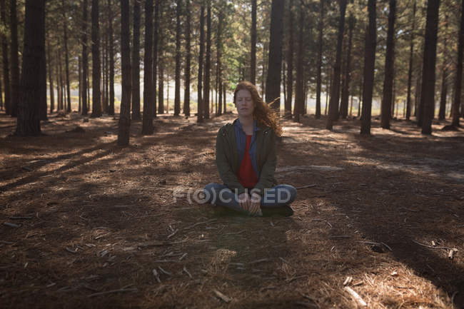 Woman doing meditation in forest on sunny day — Stock Photo
