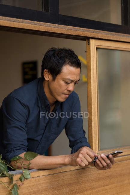 Concentrated businessman using mobile phone in the cafe — Stock Photo