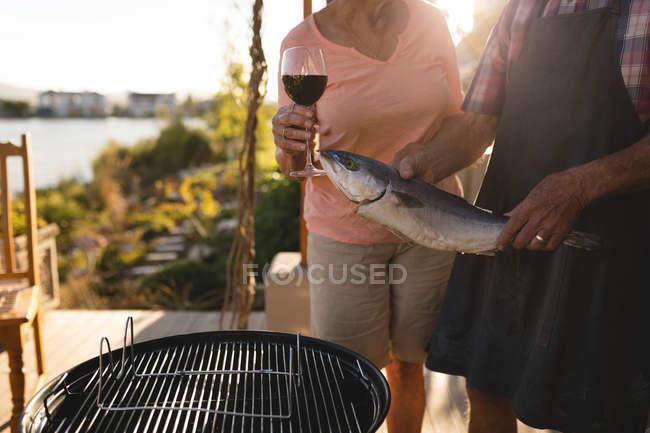 Mittleren Bereich der Älteres Paar hält Fisch und ein Glas Wein im Garten — Stockfoto