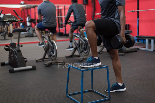 Athlete exercising with dumbbells in gym — Stock Photo