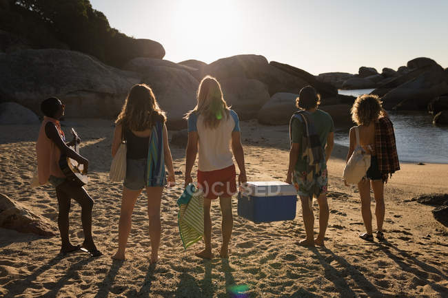 Male friends carrying esky in the beach on a sunny day — Stock Photo