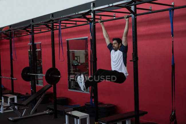 Athlete exercising on monkey bar in a gym — Stock Photo