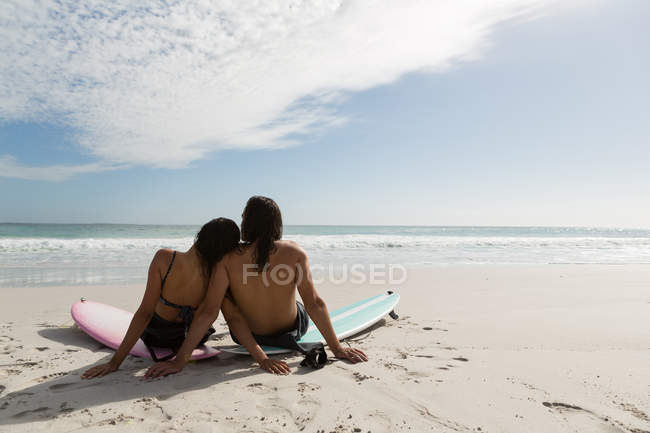 Rear view of surfer couple relaxing in the beach — Stock Photo