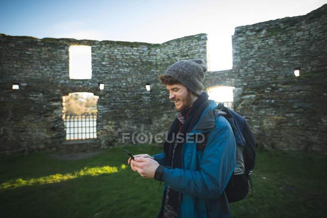 Молодой турист, использующий мобильный телефон в старых руинах в сельской местности — стоковое фото