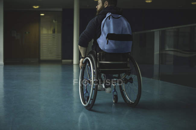 Handicapped man on wheelchair moving in passage at gym — Stock Photo