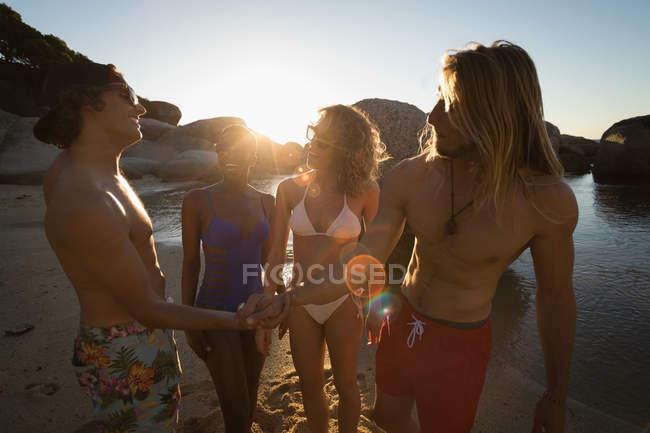 Grupo de amigos se divertindo na praia ao entardecer — Fotografia de Stock