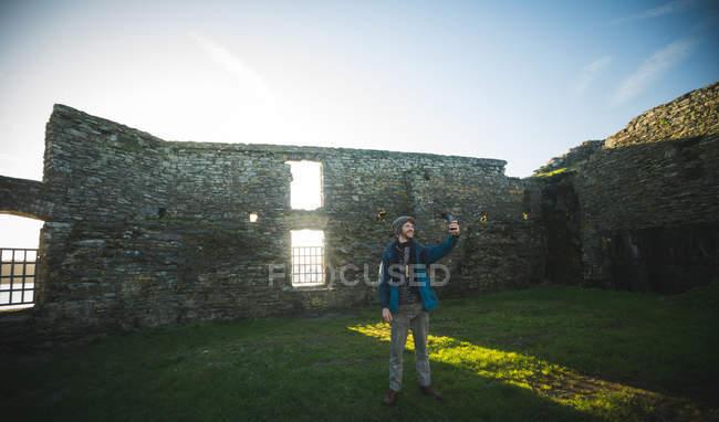Мужчина-турист делает селфи с мобильным телефоном в старых руинах в сельской местности — стоковое фото