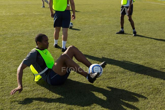 Футболіста вправ з м'ячем на полі — стокове фото