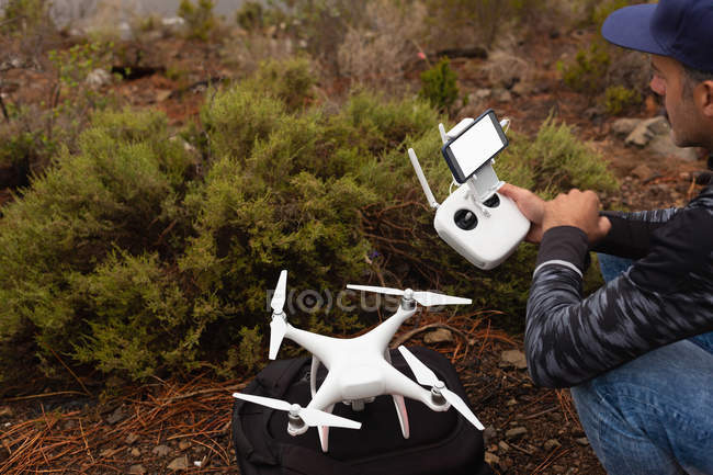Man operating a flying drone in countryside — Stock Photo