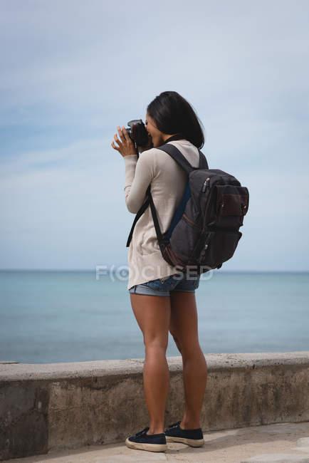 Vista trasera de la mujer haciendo clic en la foto del mar con cámara digital - foto de stock