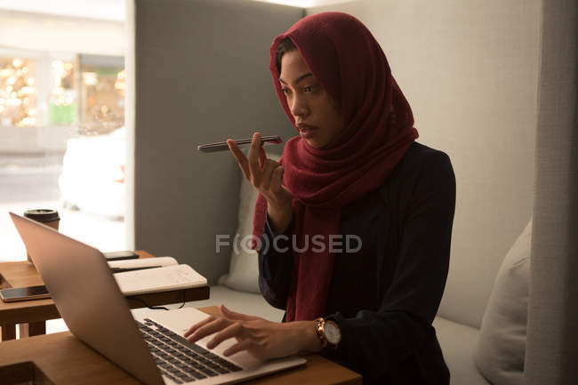 Деловая женщина в хиджабе, разговаривая по мобильному телефону в офисной столовой — стоковое фото