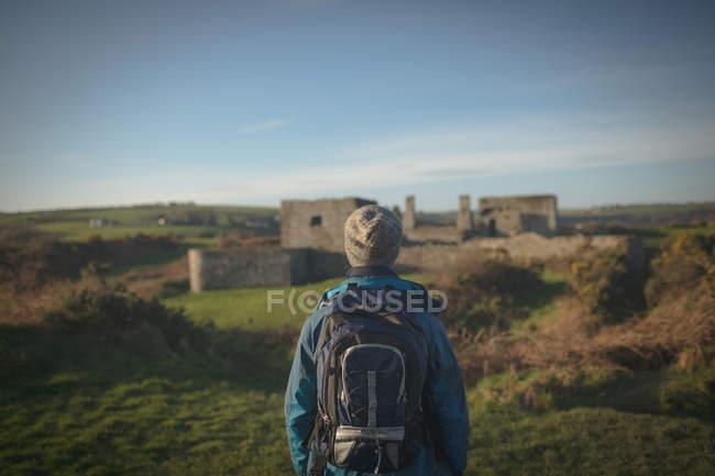 Vista posteriore del Viandante maschio in piedi con lo zaino in campagna — Foto stock