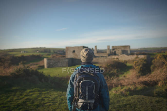 Rear view of male hiker standing with backpack at countryside — Stock Photo