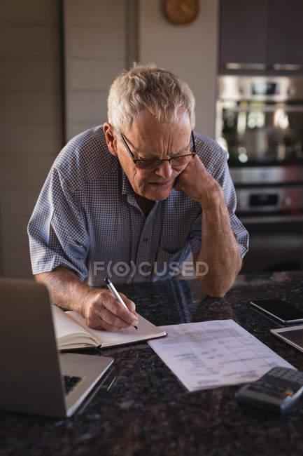 Hombre mayor activo escribiendo en un diario en el hogar - foto de stock