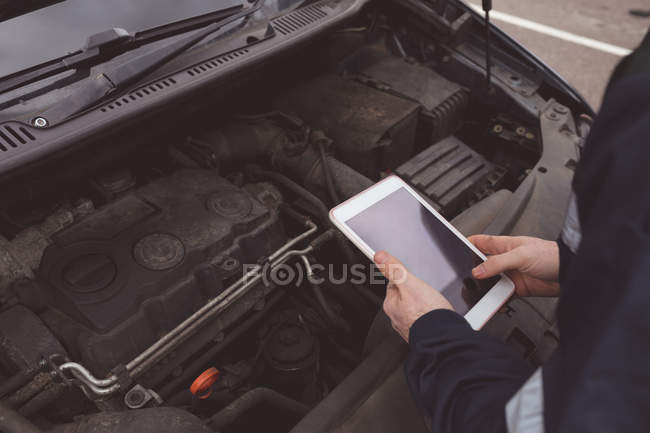 Mid section of mechanic using digital tablet at repair garage — Stock Photo