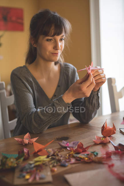 Smiling beautiful woman preparing a paper craft at home — Stock Photo