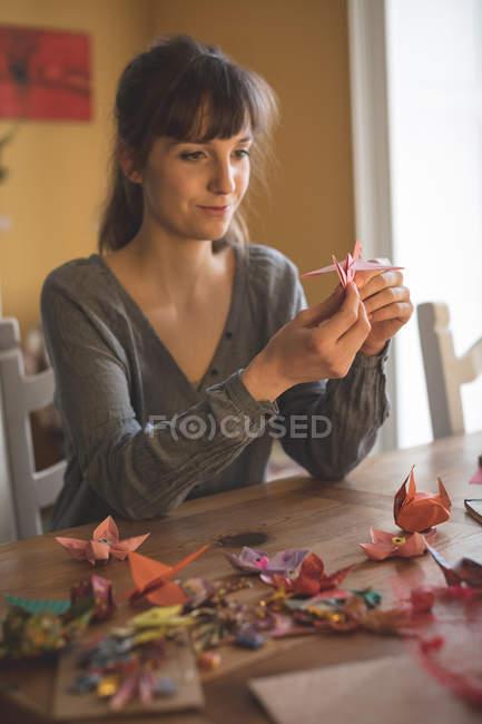 Lächelnde schöne Frau bereitet zu Hause ein Papierbasteln vor — Stockfoto