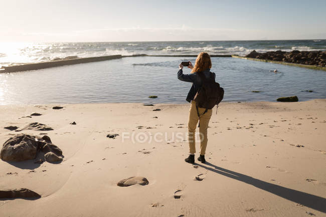 Rear view of woman clicking photo of sea at beach — Stock Photo