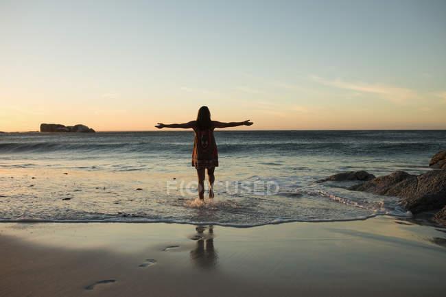 Jogadora de voleibol feminina de pé com os braços estendidos na praia — Fotografia de Stock