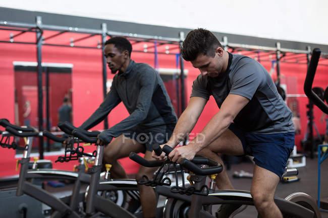 Юные спортсмены, занимающиеся на велотренажерах в тренажерном зале — стоковое фото