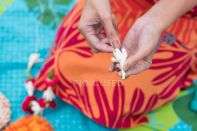 Mid section of woman preparing lei garland in the garden — Stock Photo