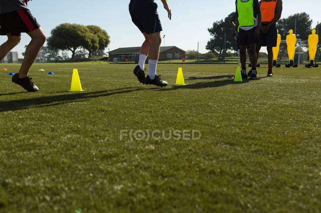 Jugadores de fútbol botando la bola a través de conos en el campo de los deportes - foto de stock