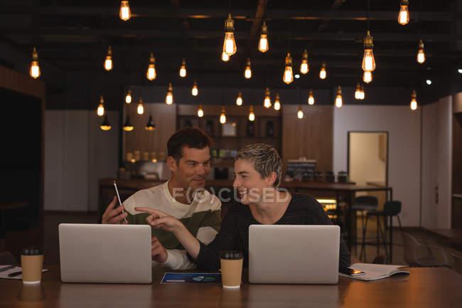 Collègues de travail, discuter au téléphone mobile dans la cafétéria du Bureau — Photo de stock