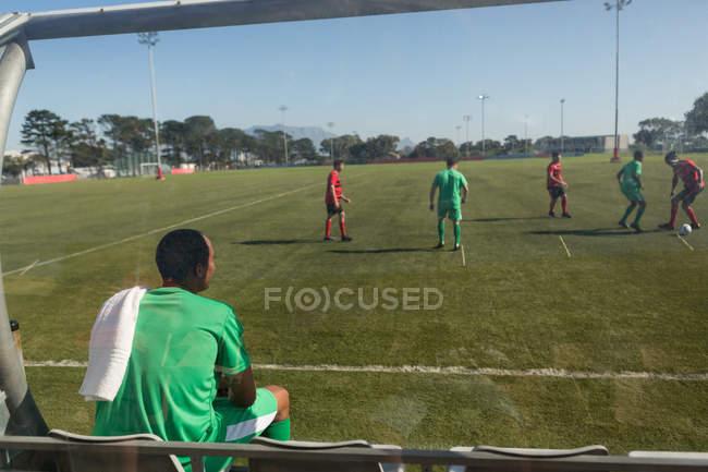Vista trasera del jugador viendo el partido de fútbol desde dugout - foto de stock