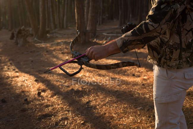 Metà sezione di cacciatore pronto a sparare con arco e freccia nella foresta — Foto stock