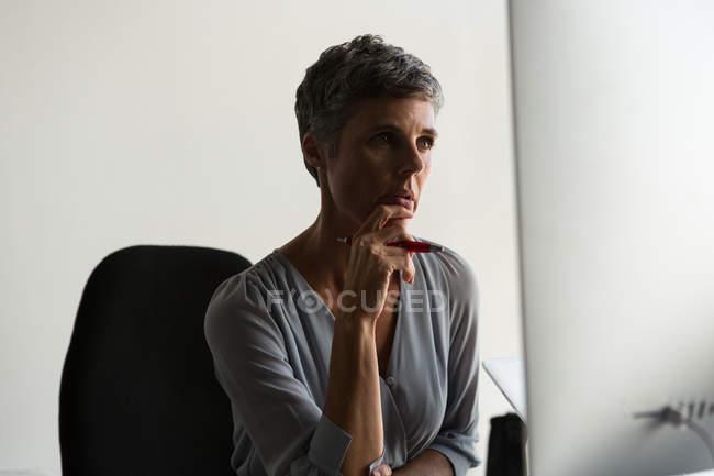 Продуманий зрілих бізнес-леді дивлячись на комп'ютері в офісі — стокове фото