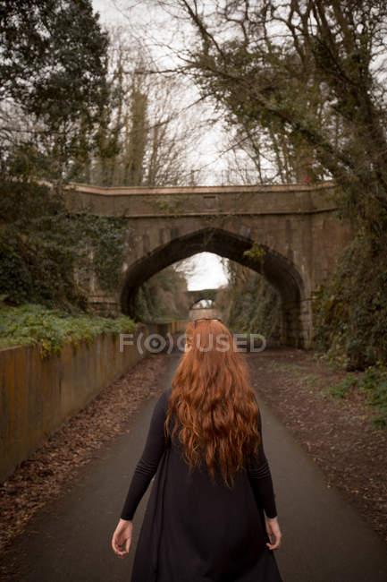 Vue arrière d'une femme marchant sur une route de campagne — Photo de stock