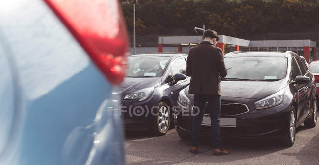 Rear view of salesman standing next to car outside the showroom — Stock Photo