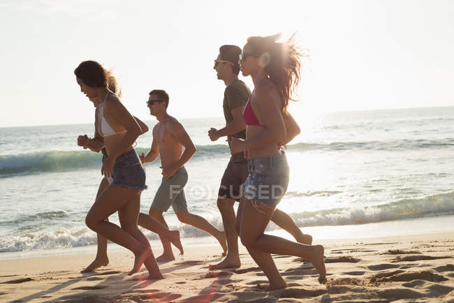 Group of friends running in the beach at dusk — Stock Photo