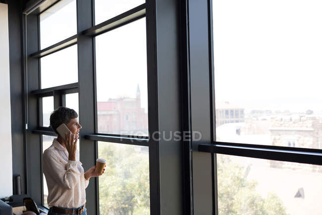 Mature businesswoman talking on mobile phone while having coffee in the office — Stock Photo