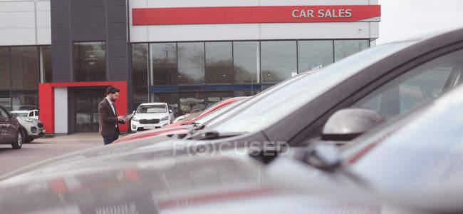 Продавец, стоящий рядом с машиной и читающий брошюру возле выставочного зала — стоковое фото