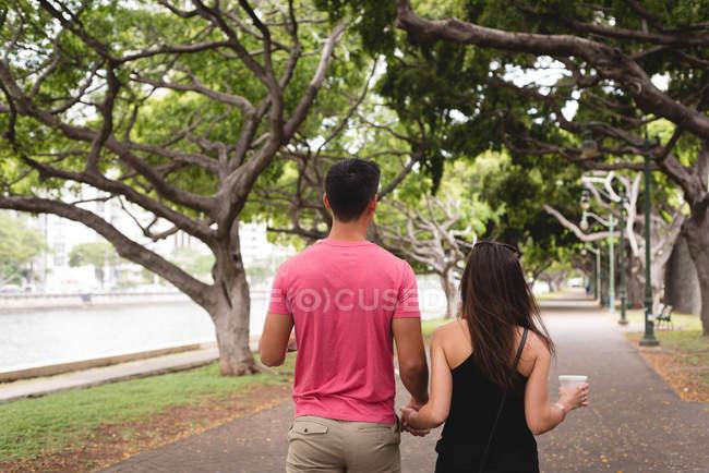 Rückansicht eines Paares, das Hand in Hand auf einem Gehweg geht — Stockfoto