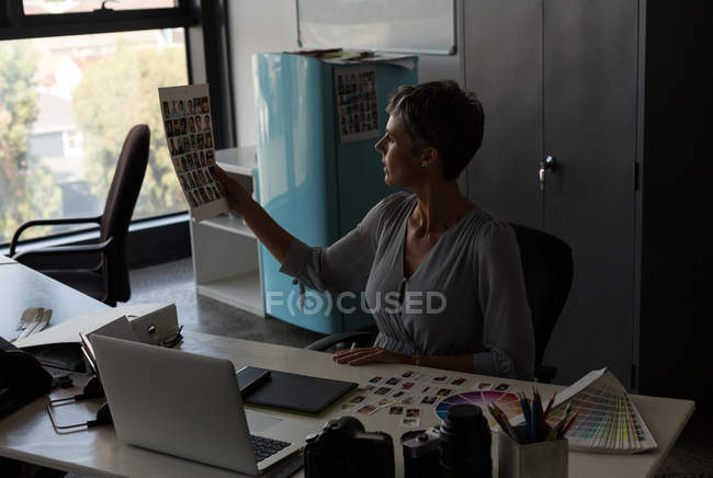 Graphic designer checking photograph in the office — Stock Photo