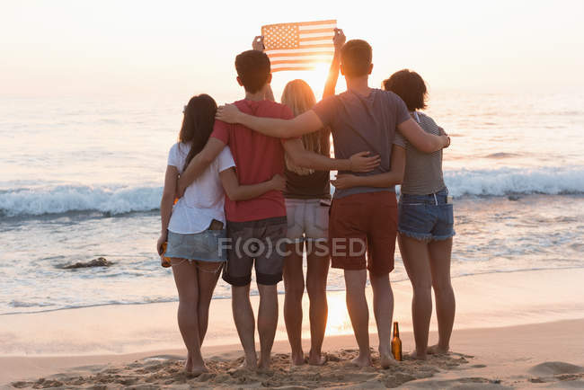 Group of friends holding american flag in the beach at dusk — Stock Photo