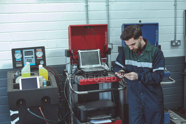 Attentive mechanic using mobile phone in repair garage — Stock Photo