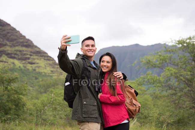 Casal feliz tomando selfie com telefone celular no campo — Fotografia de Stock