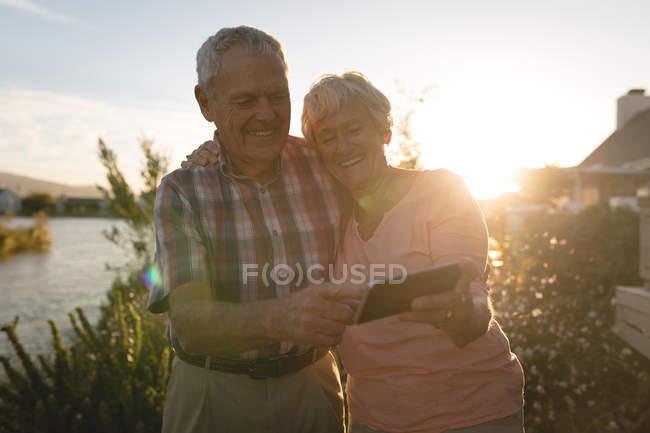 Happy senior couple using mobile phone in the backyard — Stock Photo