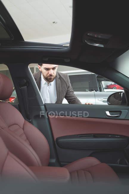 Красивий продавець, розглядаючи в салоні автомобіля — стокове фото