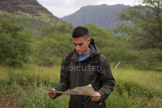 Young man looking at map in countryside — Stock Photo