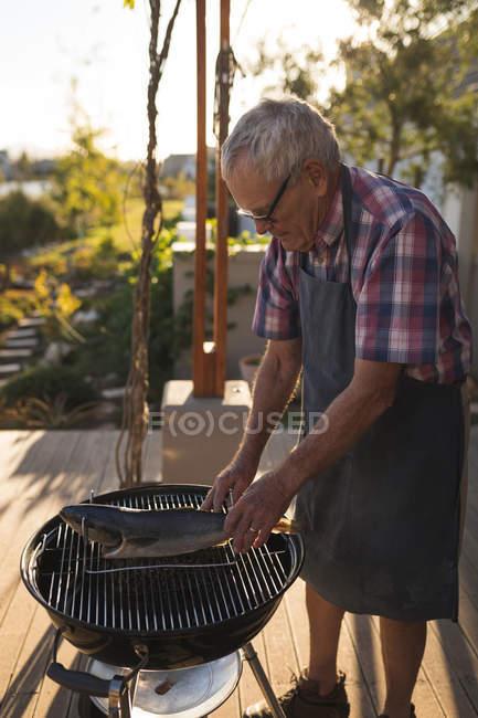 Senior woman Kochen Fisch am Grill im Garten — Stockfoto