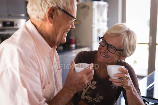 Пожилые супружеские пары, улыбаясь имея кофе на кухне дома — стоковое фото