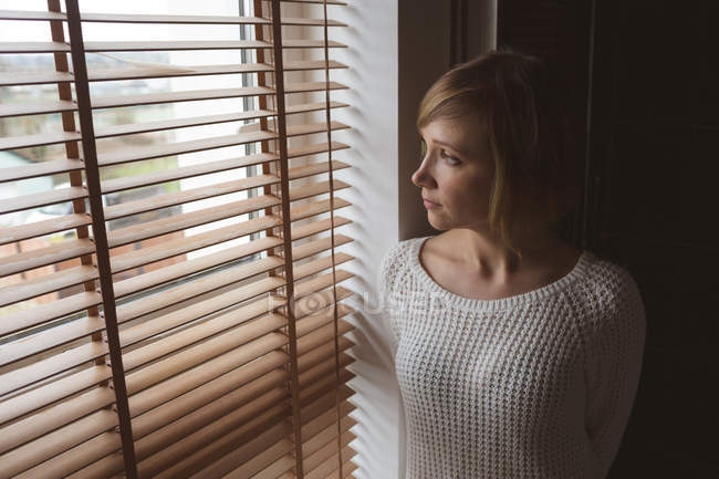 Beautiful woman looking through window blinds at home — Stock Photo