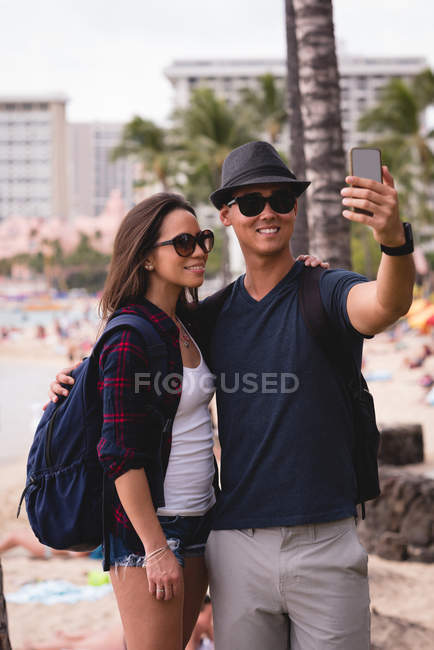 Happy couple taking selfie with mobile phone near beach — Stock Photo
