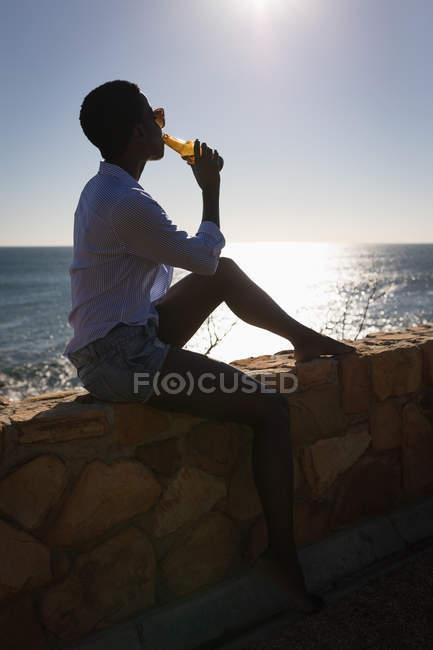 Femme buvant de la bière à la plage par une journée ensoleillée — Photo de stock